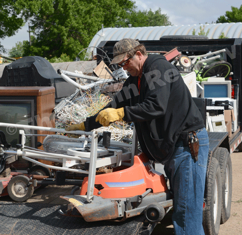 Jerry Finkrel loads up metal junk to a trailer to be hauled away. E-R photo