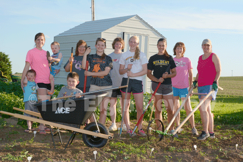 "Posing in front of their new garden shed and with some of their new gardening tools are Cedar Creek club members and parents, l-r:  Sawyer Veik, Heather Veik, Myles Veik, Landyn Veik (in wheel barrow), Lori Beckman, Erin Beckman, Diane Nelson, Amy Nelson, Grace Henn, Sandi Henn and Anne Meis. The club was able to purchase the new equipment with grant monies recently received from Farm Credit Services of America's ""Working Here Fund"". E-R photo"
