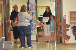Pam Wright takes a photo of her daughter Megan with first grade teacher Dianne Gunderson (kindergarten teacher Brenda Siems is lookign on)