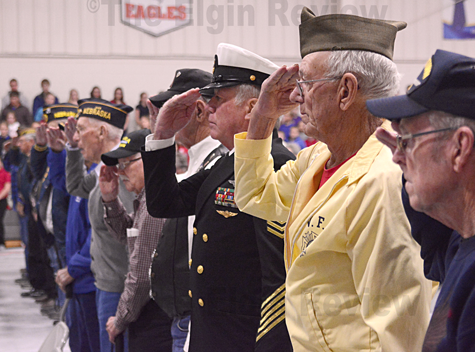 Veterans in attendance salute the flag. The Elgin Review
